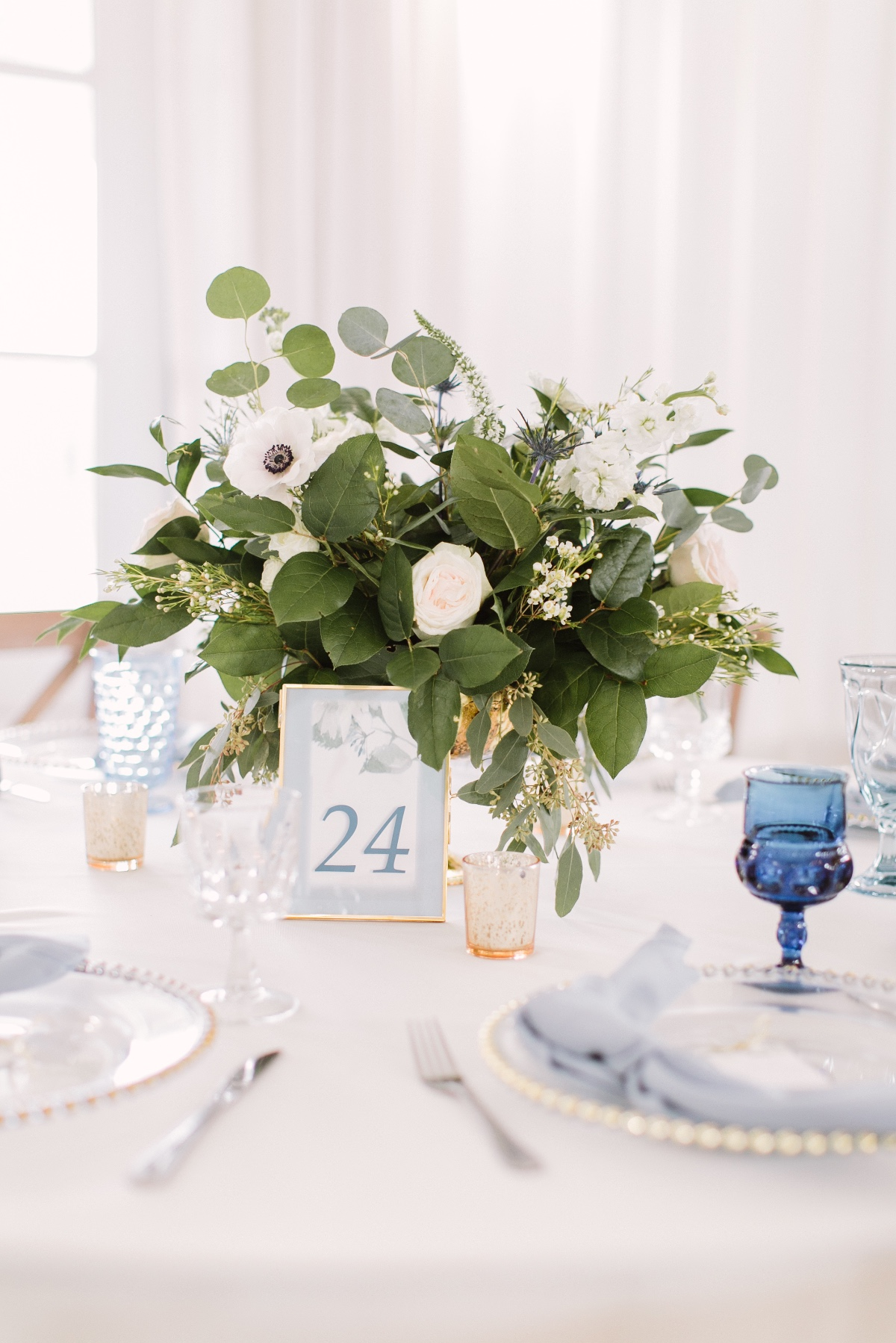 white and blue table decor with green and white floral arrangement