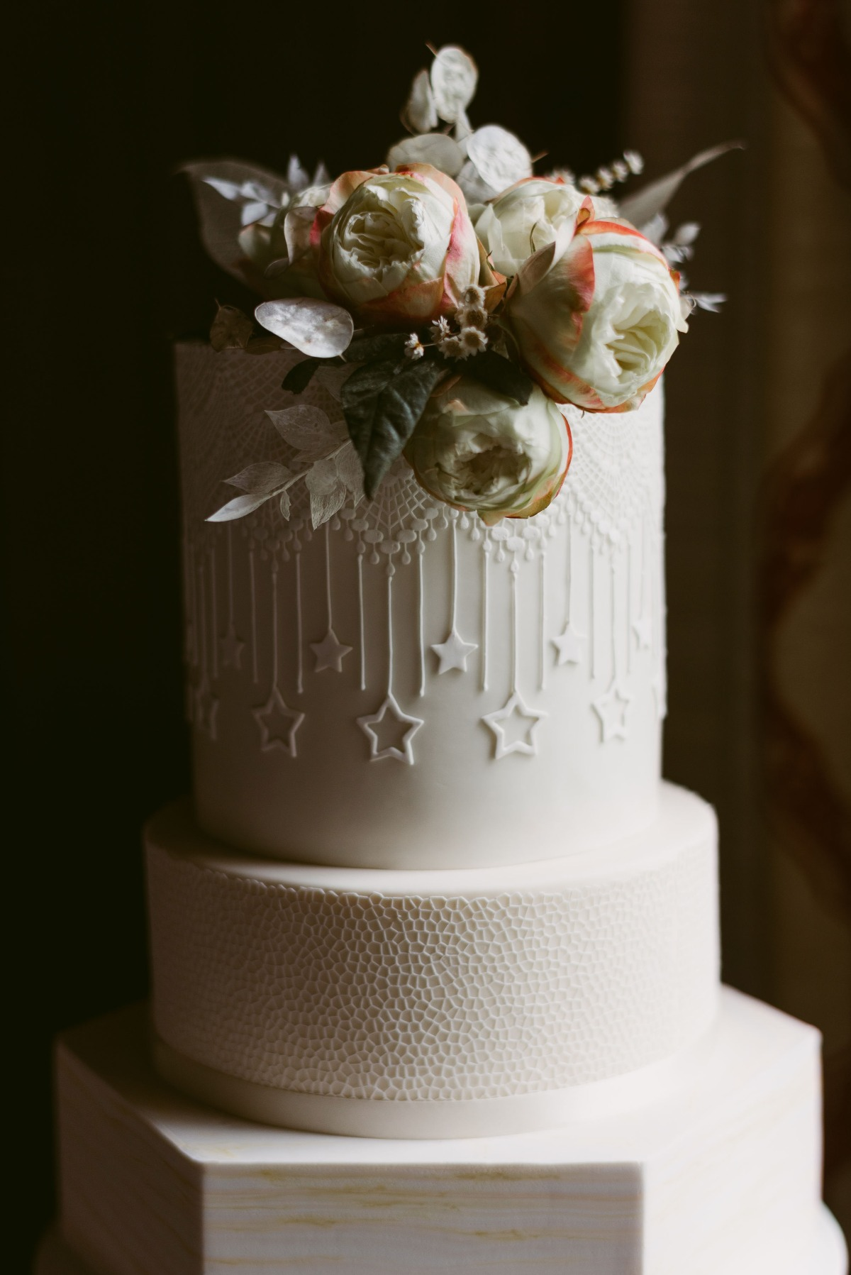 white wedding cake with stars and texture by The Fancy Cake Box