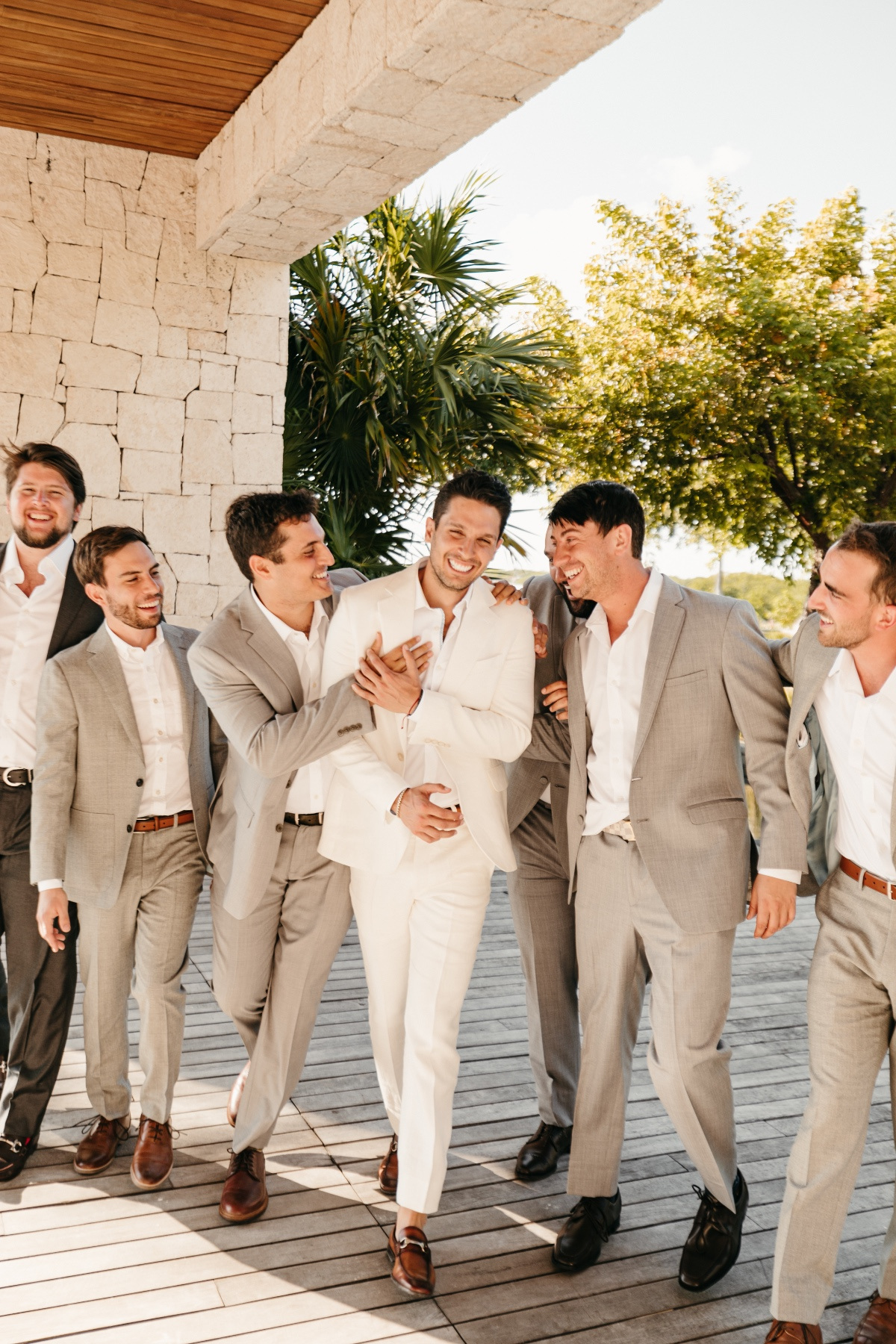 Groomsmen in linen suits with white shirts and brown shoes