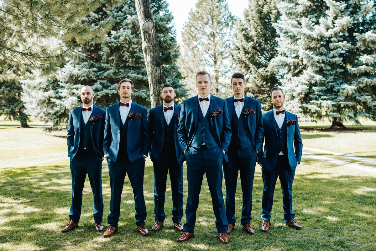 Groomsmen in navy suits with berry velvet bow ties