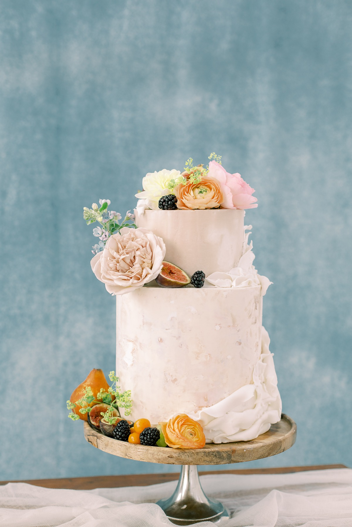 white wedding cake adorned with florals