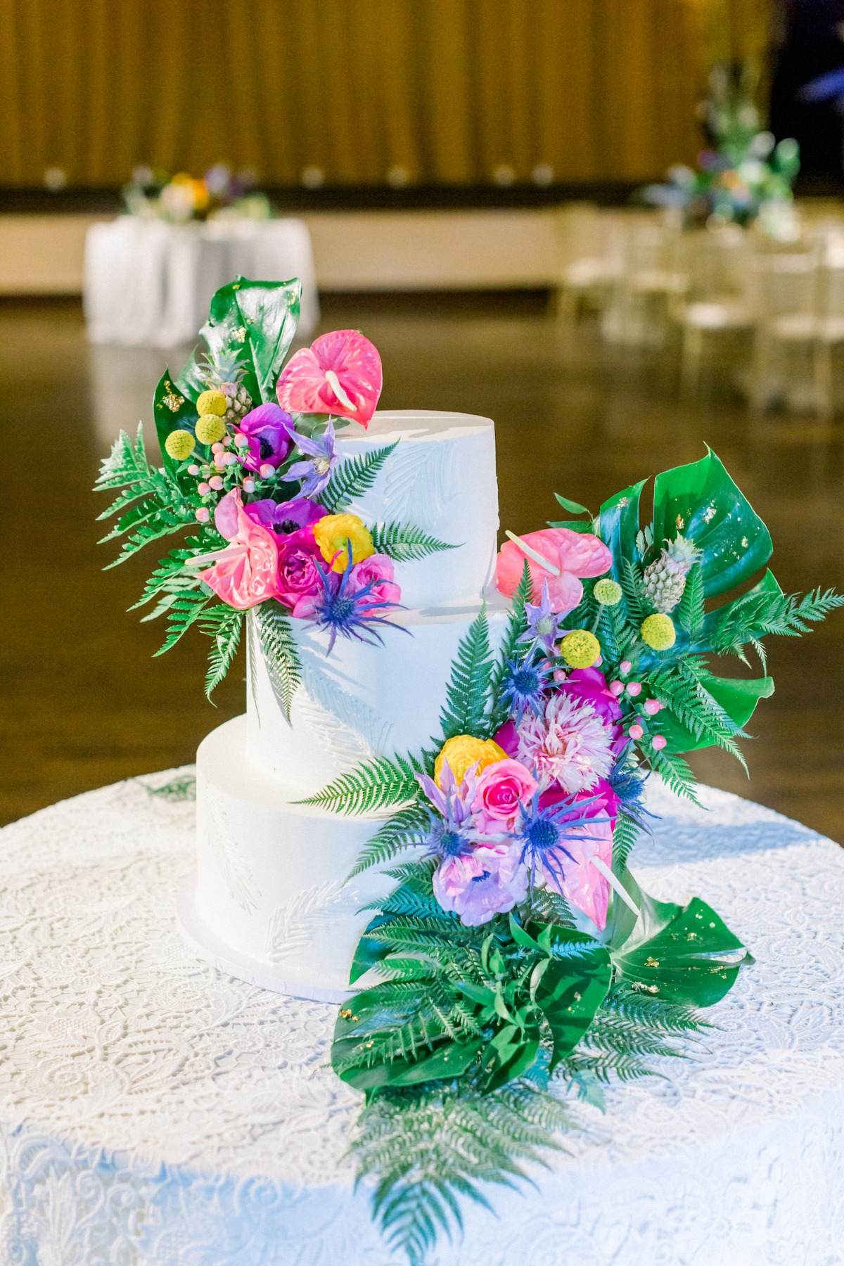 white wedding cake adorned with tropical flowers