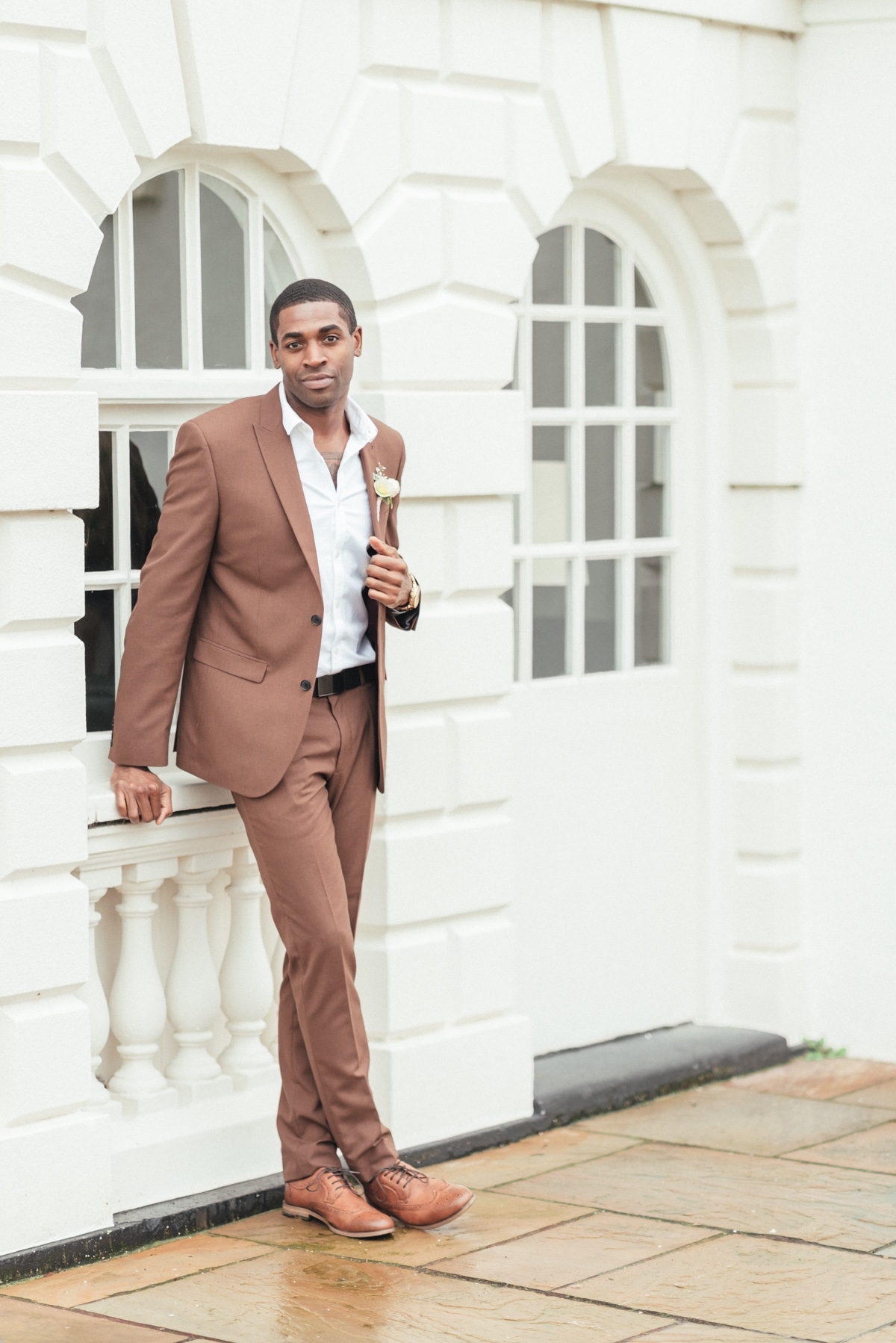 Groom in brown suit with brown shoes and pink boutonniere