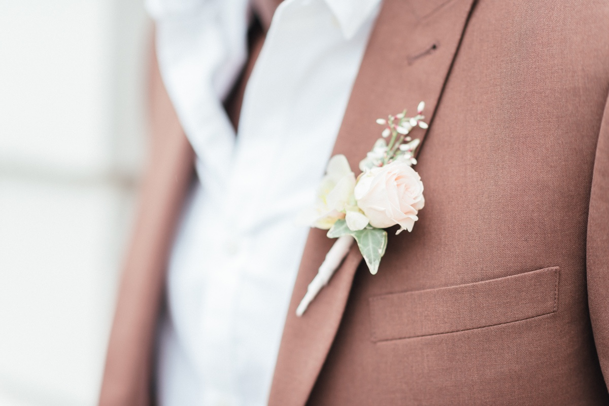 pink boutonniere  paired with brown suit
