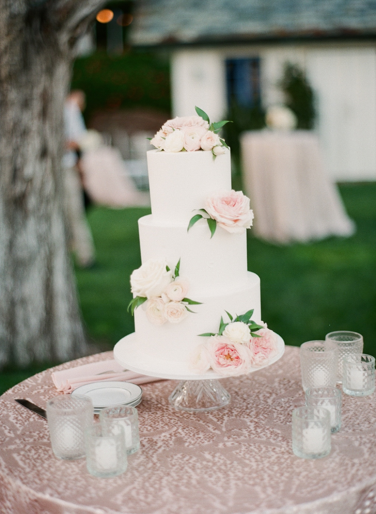 white wedding cake adorned with pink flowers