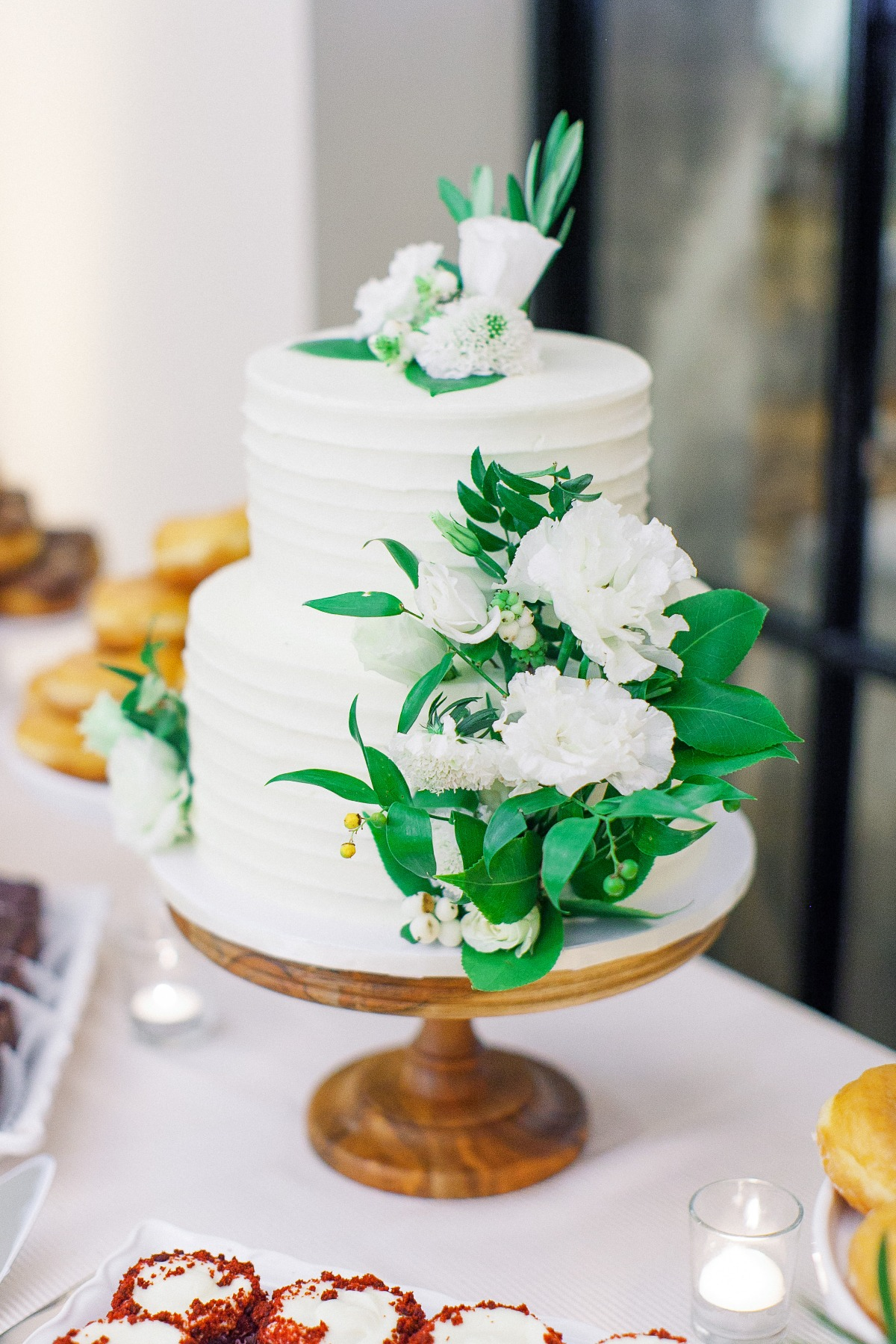 white wedding cake with green and white florals