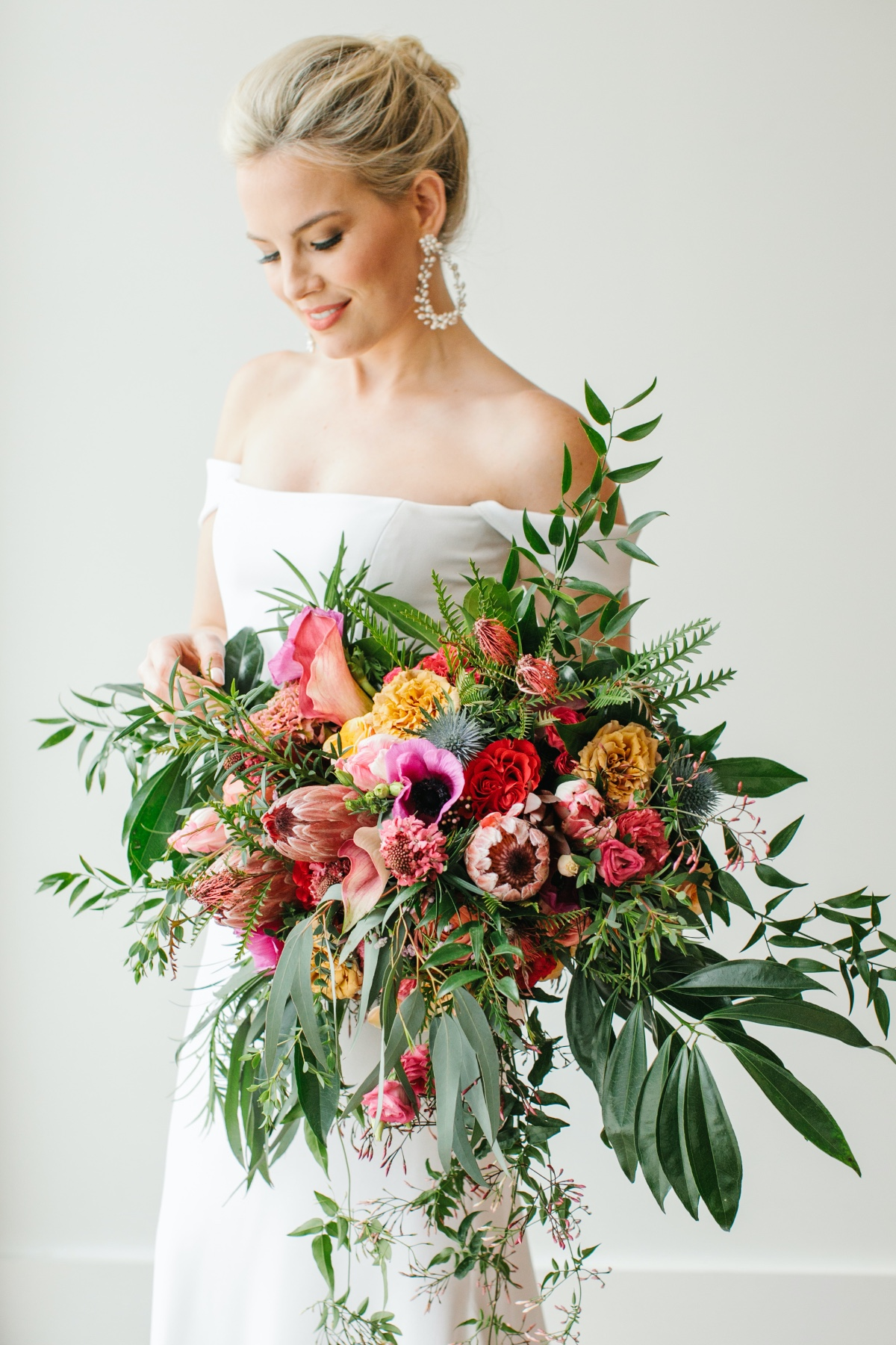 lose wedding bouquet with protea, pink anemone, greenery and tropical florals