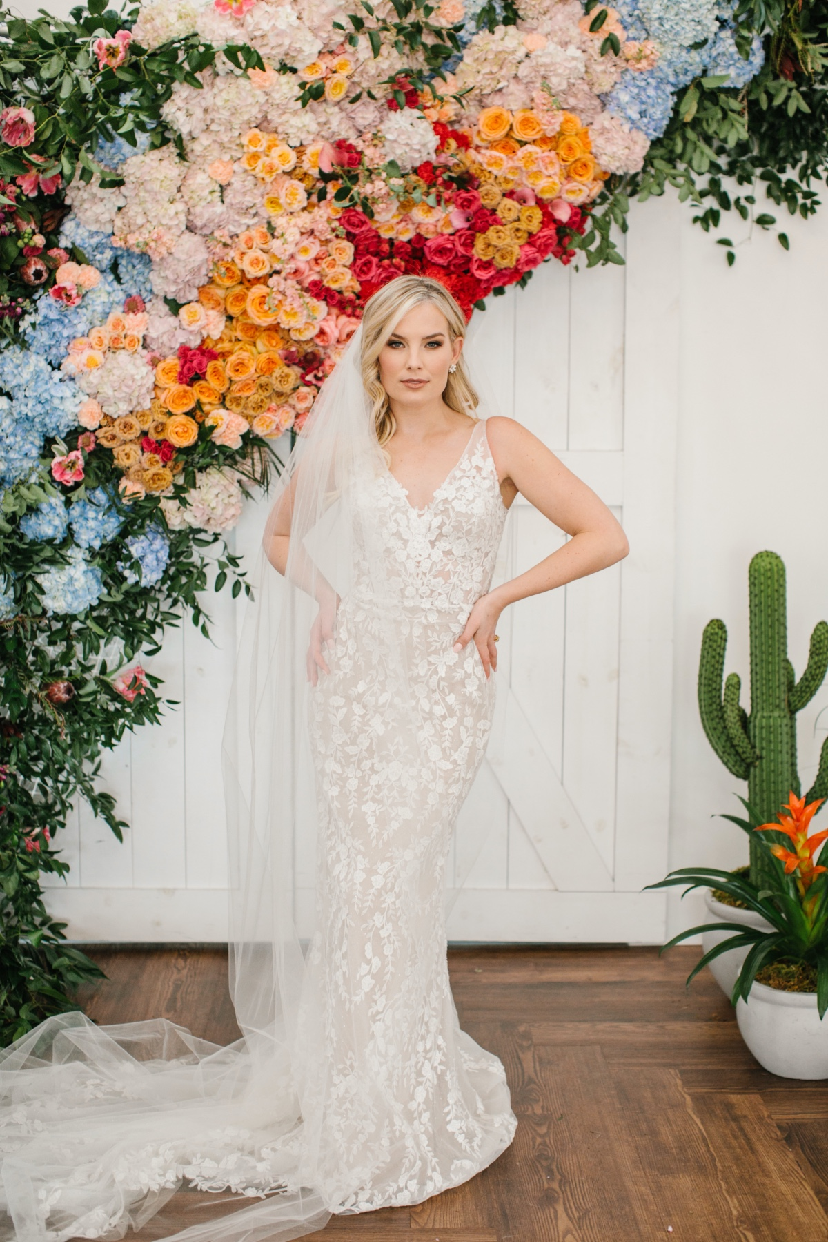 Lace wedding gown in front rainbow floral backdrop