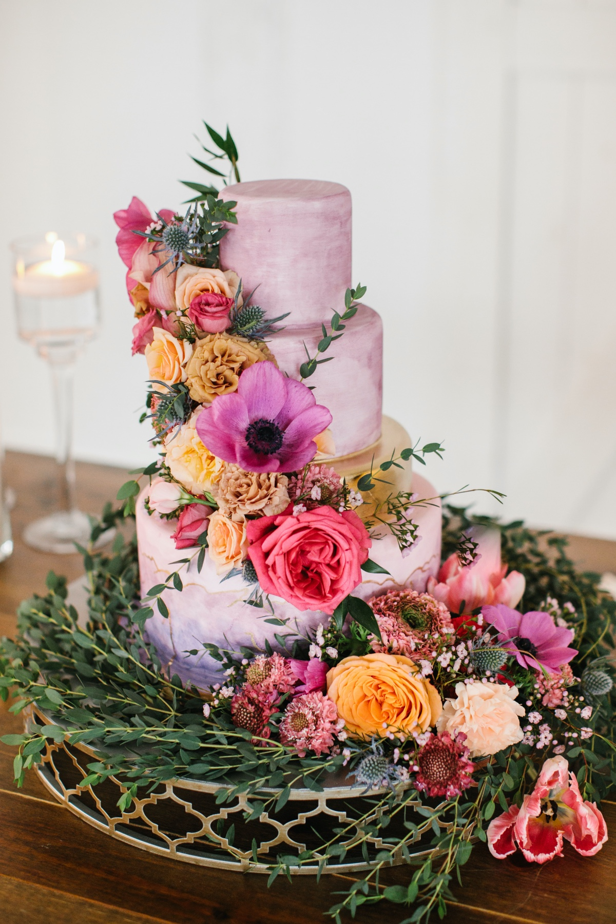 purple watercolor wedding cake adorned with florals from Baked in Nashville