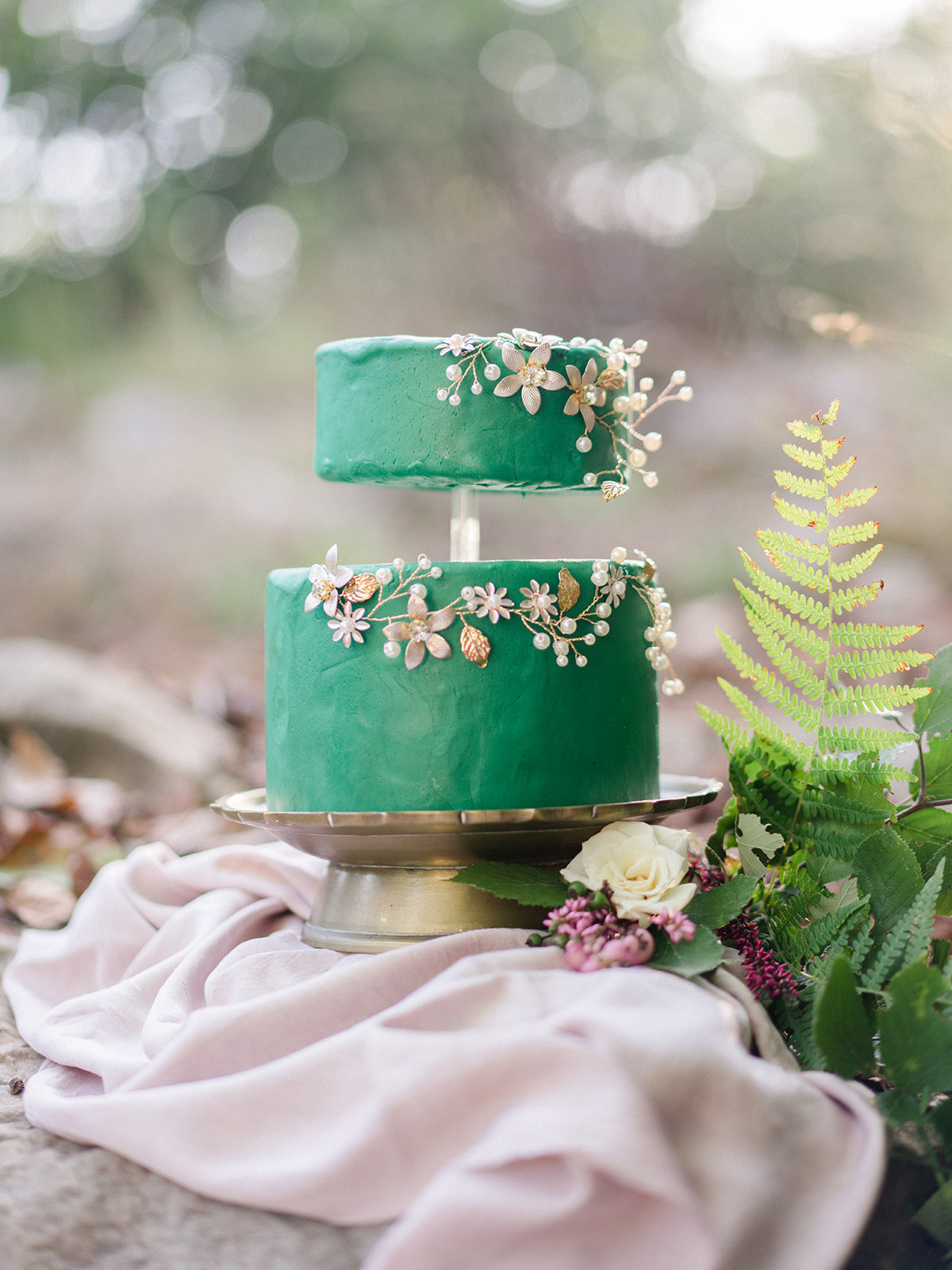 green wedding cake on gold cake stand