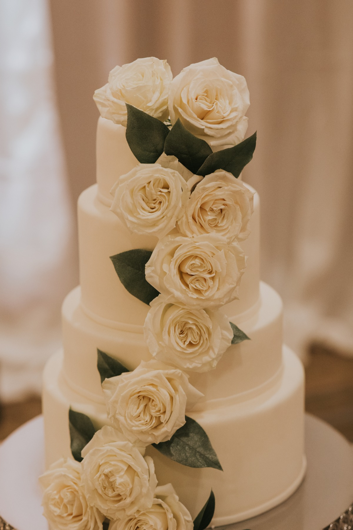 white wedding cake adorned with fresh white roses