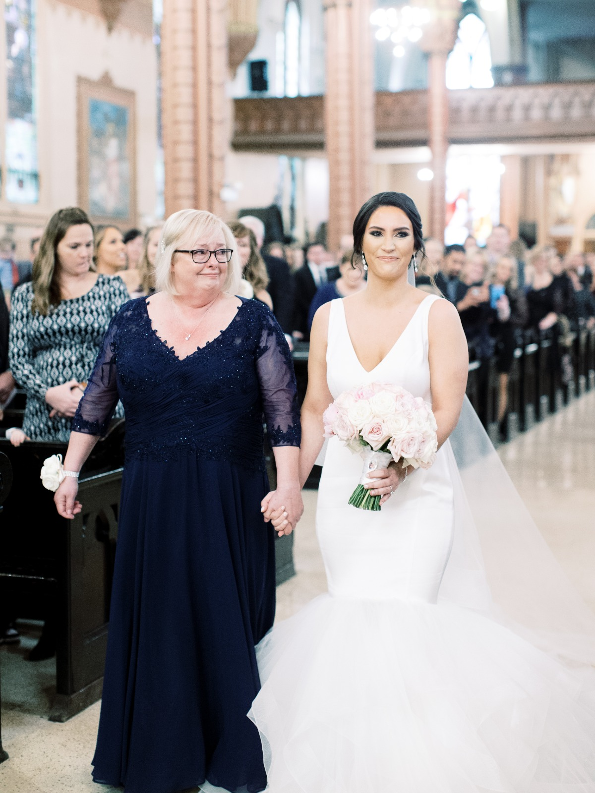 Mom walking daughter down the aisle at wedding