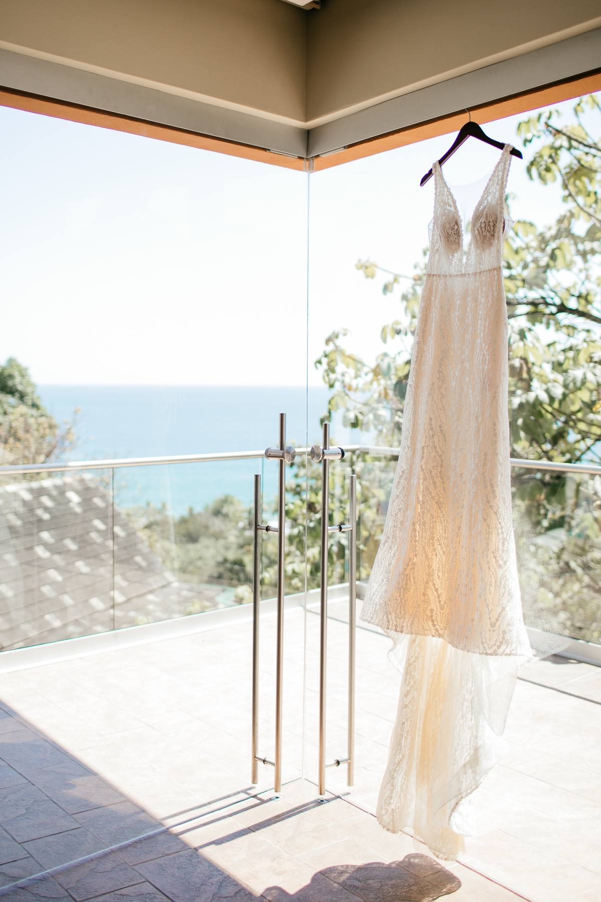 wedding dress hanging with ocean in the background