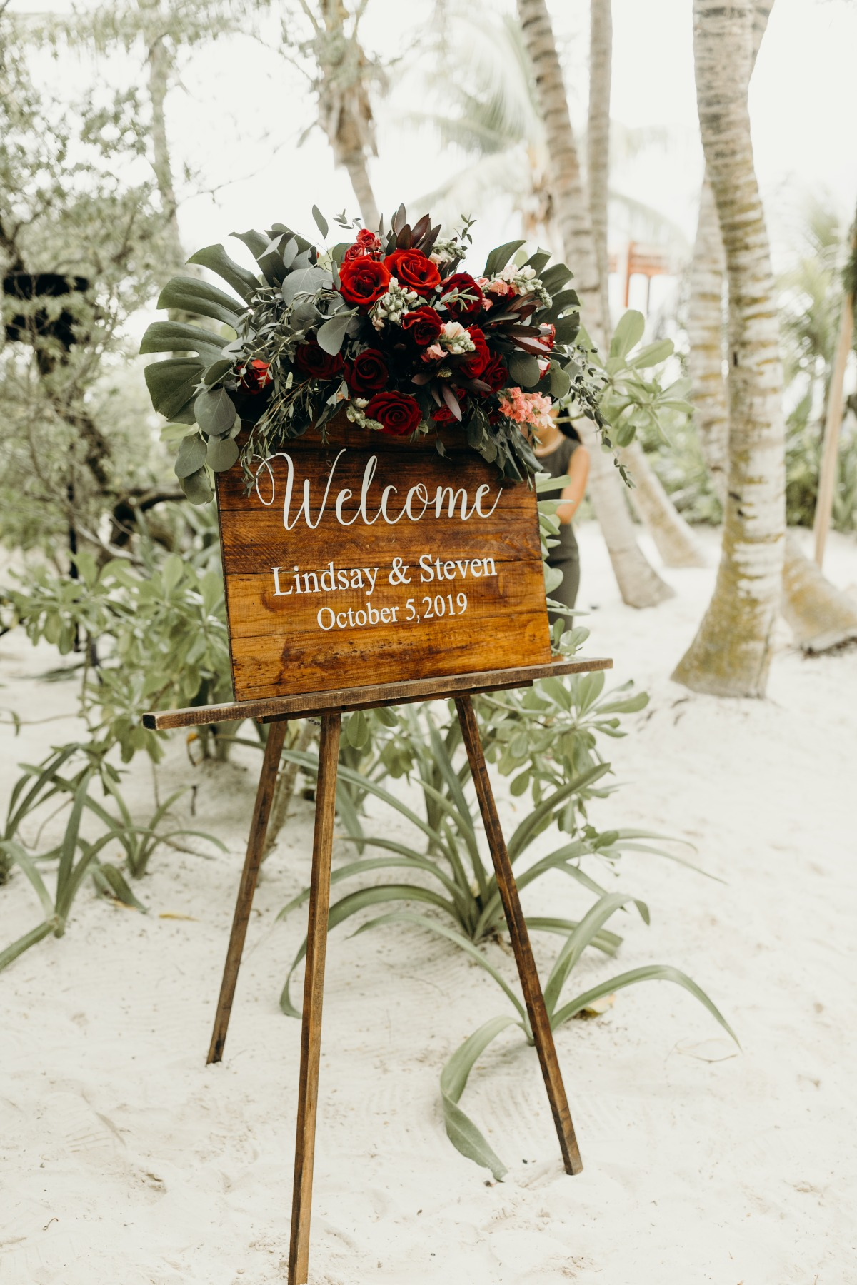 wooden welcome wedding sign with tropical floral arrangements