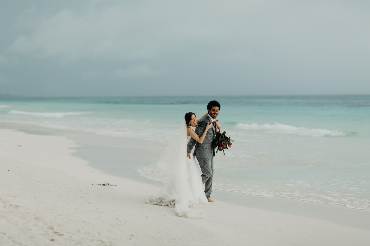 bride and groom walking on beach in Tulum, Mexico