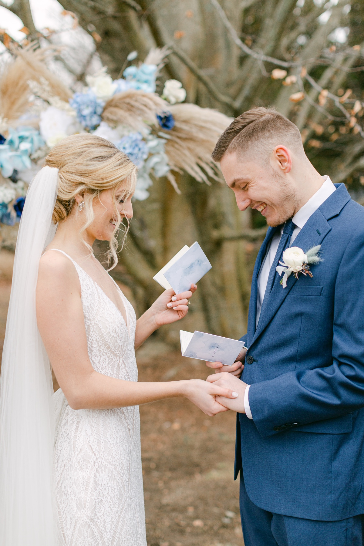 couple holding blue wedding vow books