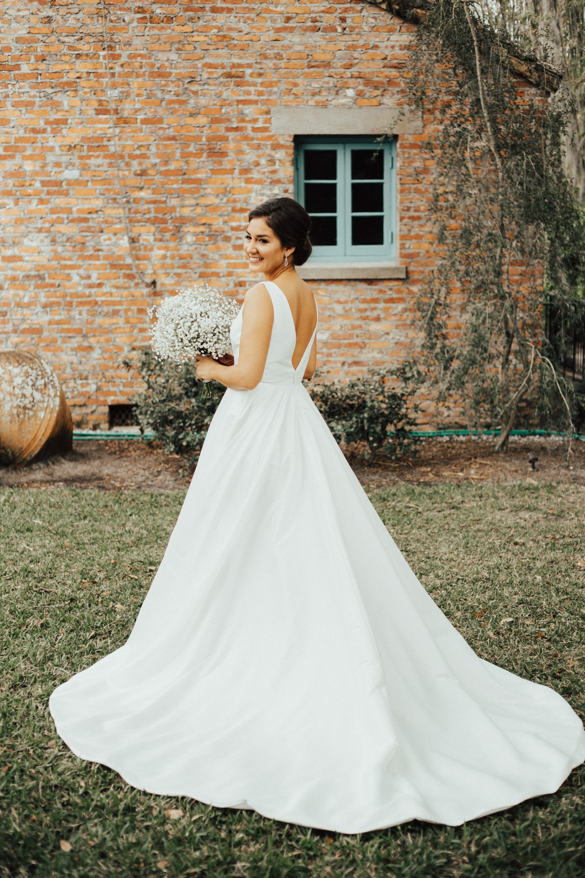 Classic Bridal Gown with thicker straps holding a baby's breath bouquet