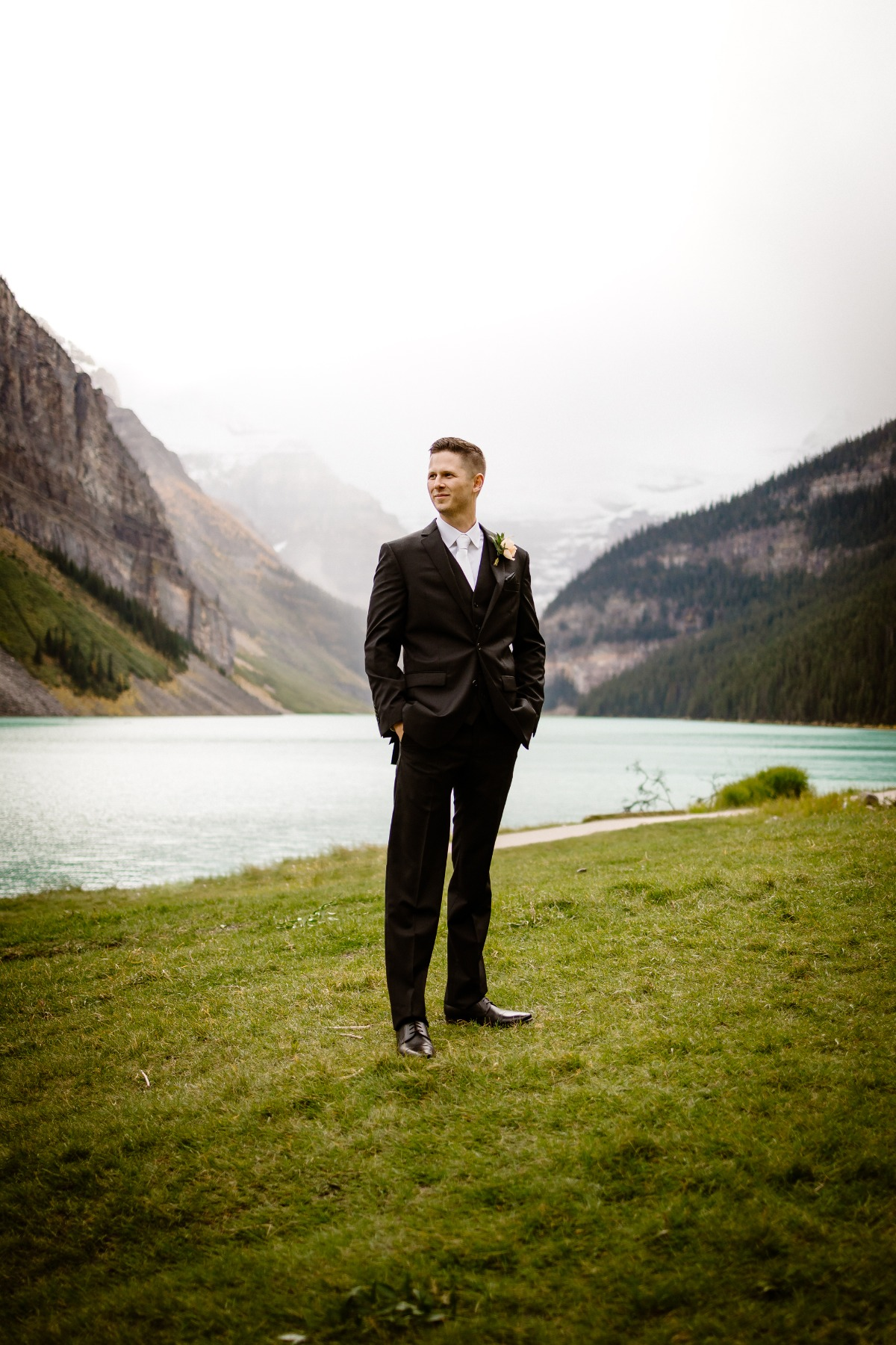 Groom in front of Lake Louise in Banff National park