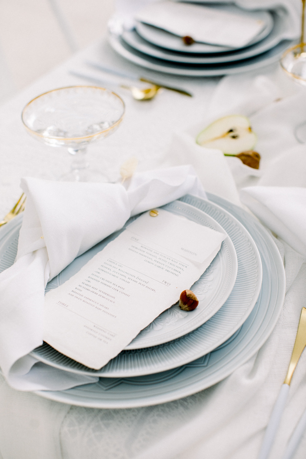 white table setting with gold cutlery and coupe Champagne glasses