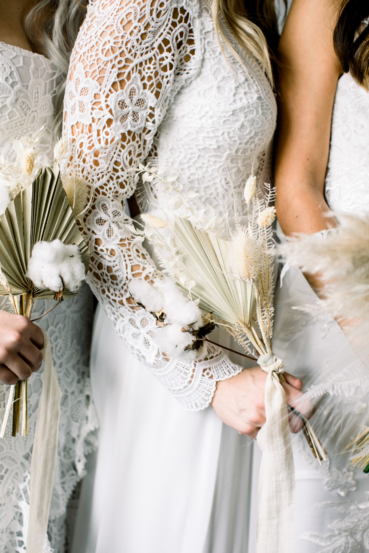 bridesmaids in white dresses holding pampas grass wedding bouquets