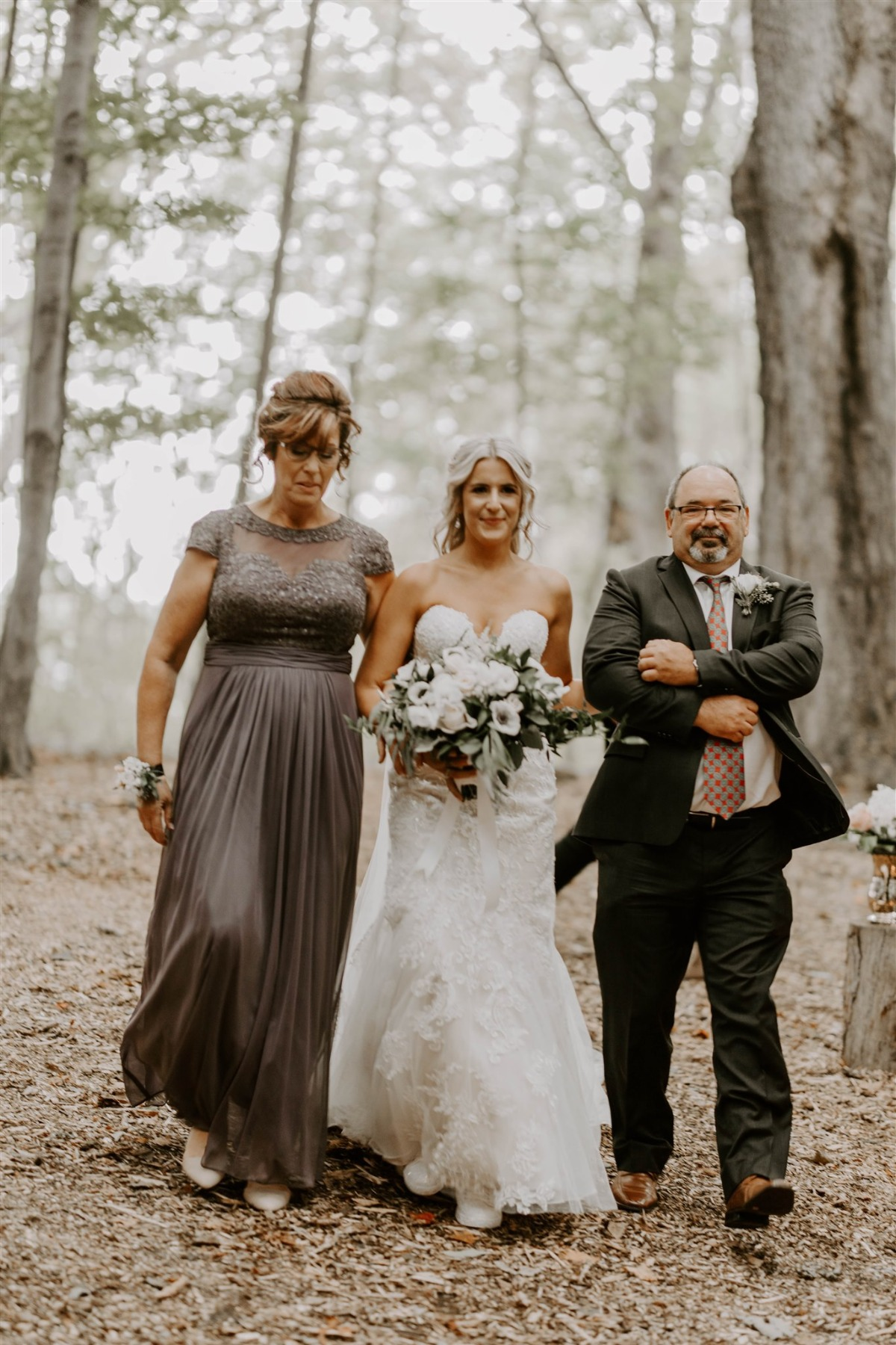bride being walked down the aisle by Mom and Dad