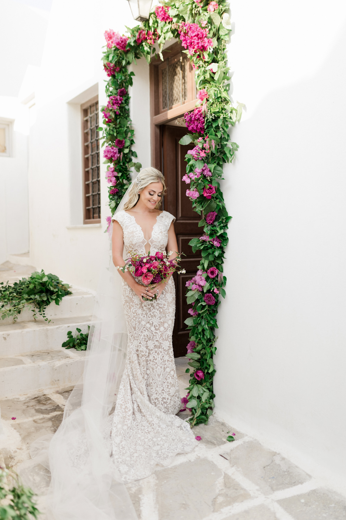 bride in door way adorned with greener and magenta florals