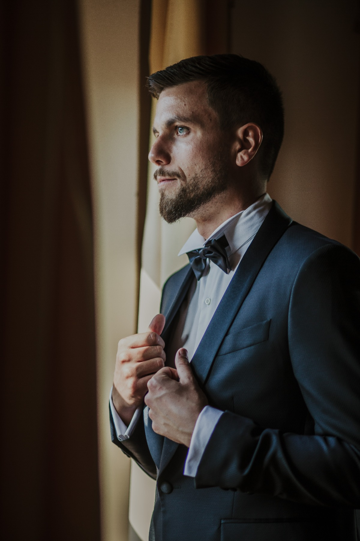 Groom in navy blue tux with black bow tie