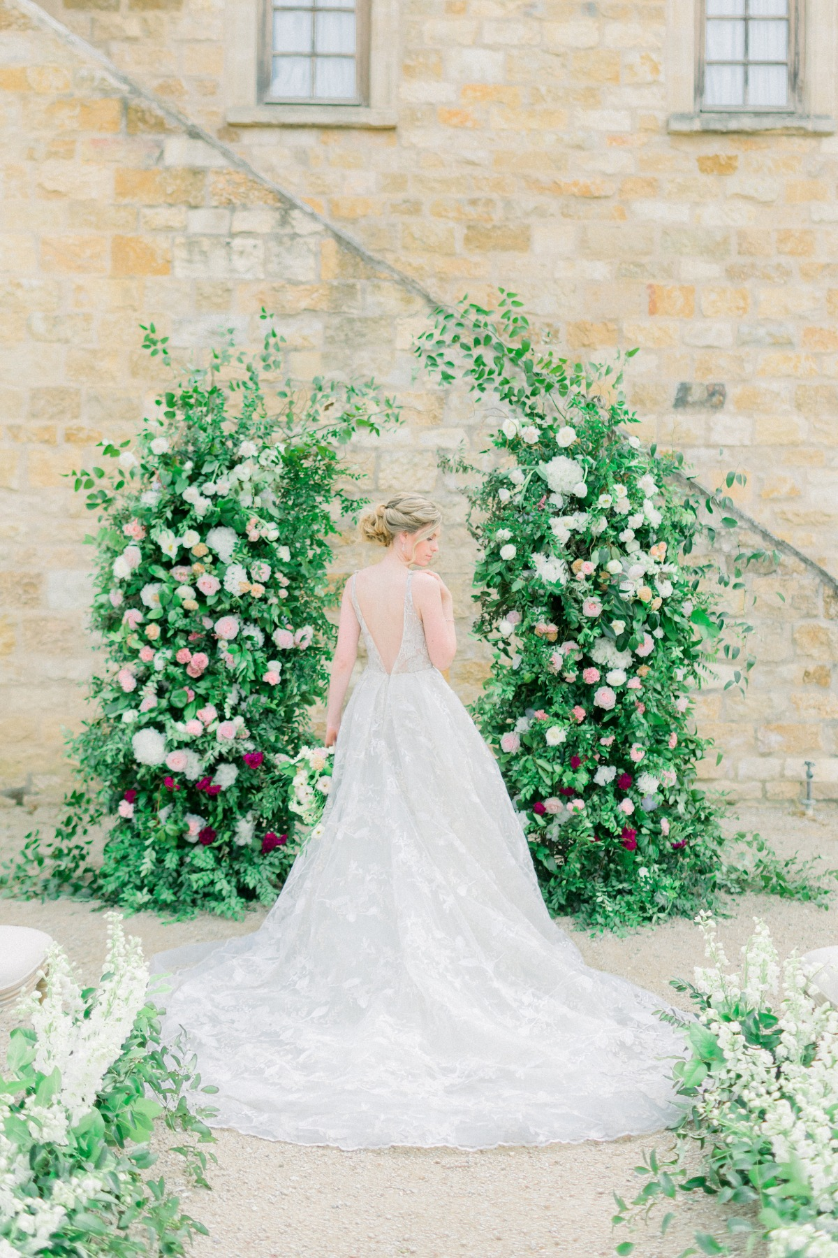Hailey Paige Bridal wedding gown in front of organic floral backdro[