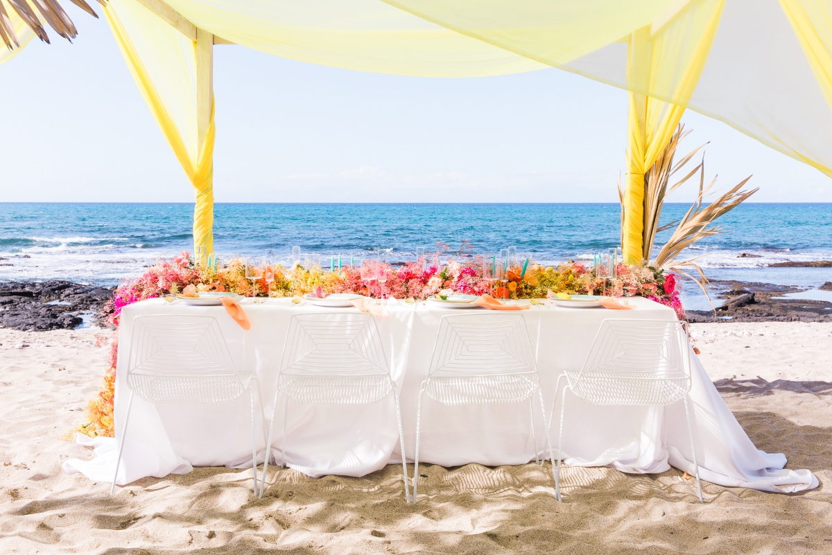 rainbow floral table runner at beachside wedding reception