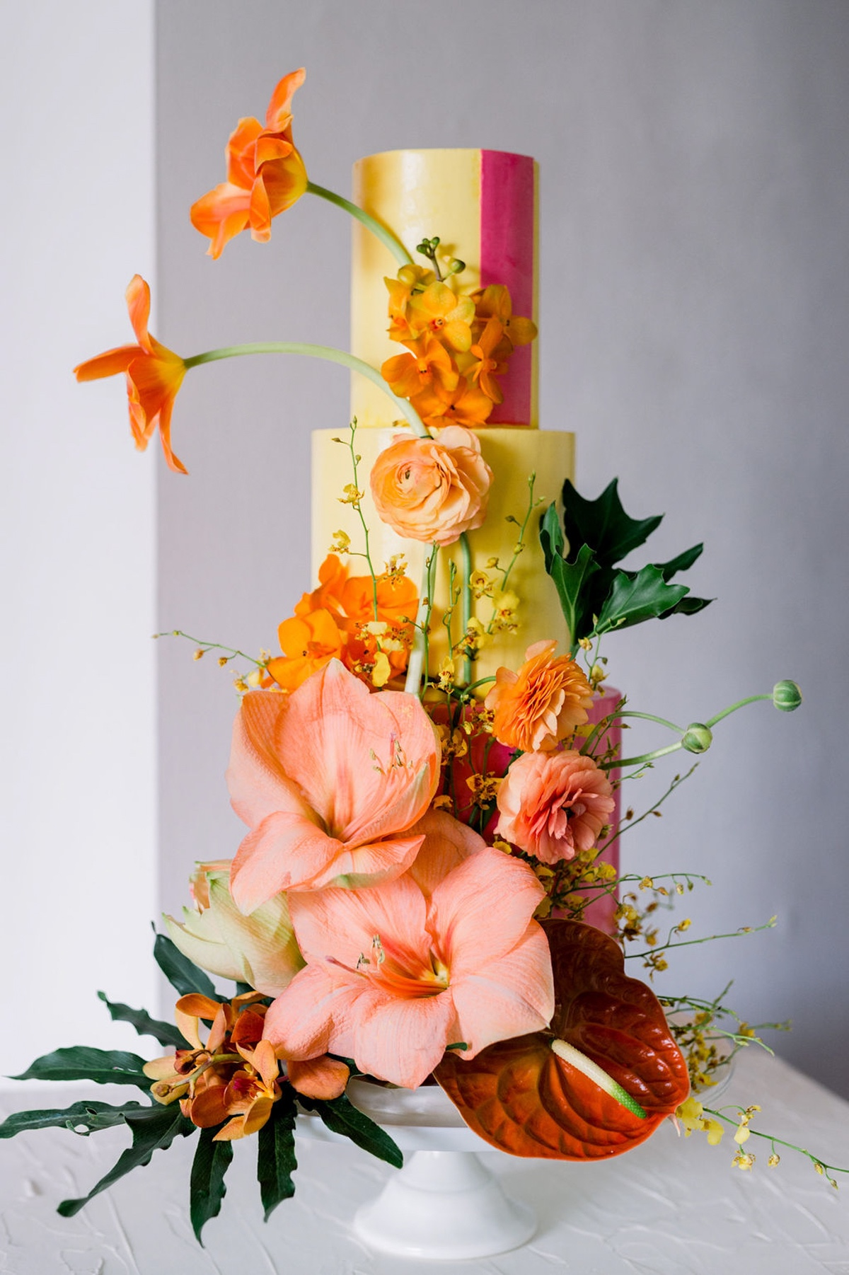 bright and colorful wedding cake adorned with tropical flowers