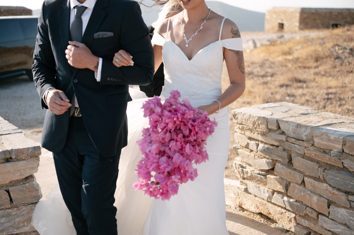 bride walking at Greece ceremony site, theater of Odysseus Elytis with bougainvillea bouquet