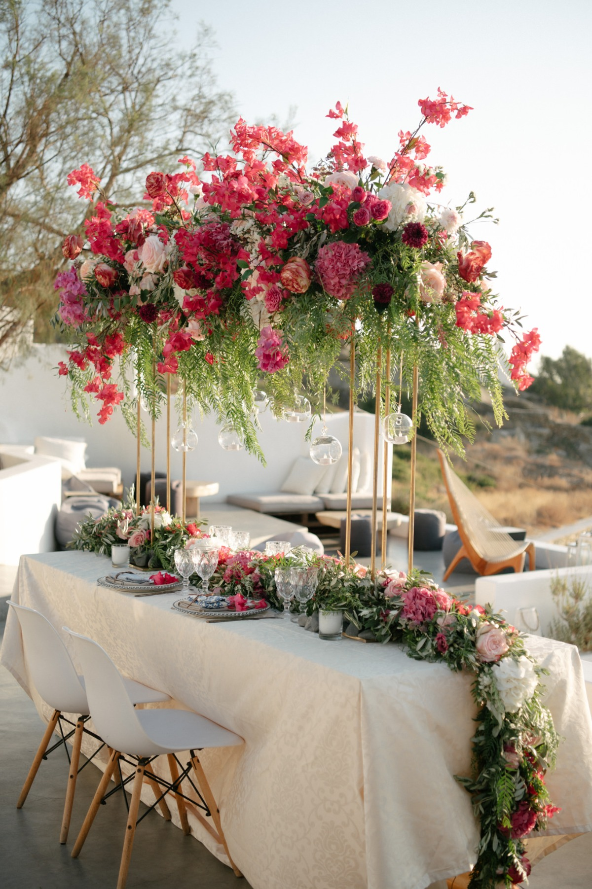 shades of pink tall centerpiece with tea lights hanging from the arrangement