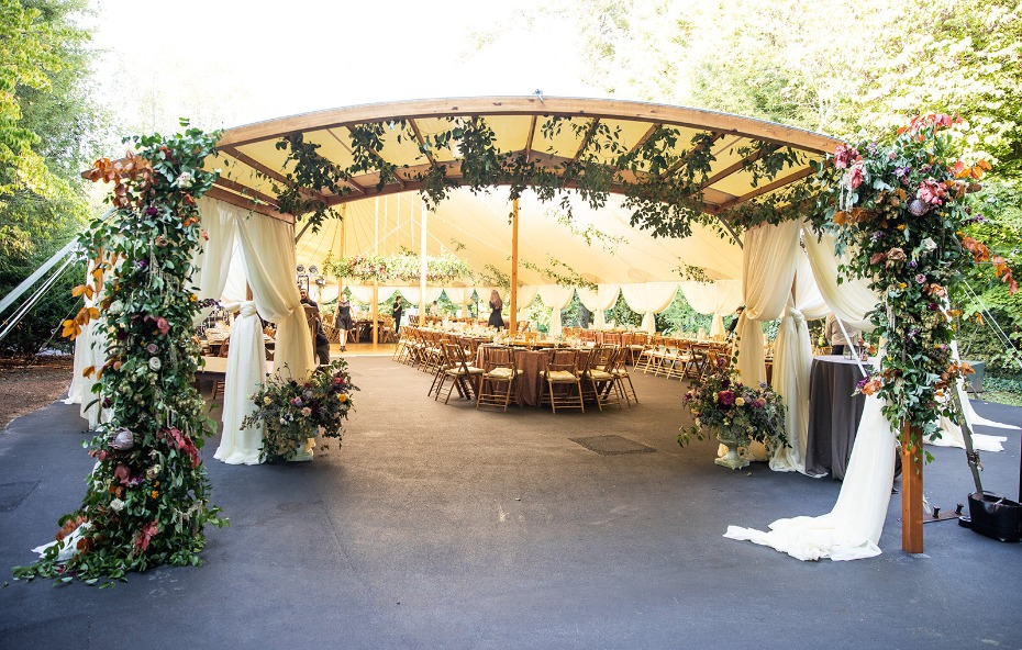 Tent entrance flower installation with lush vines