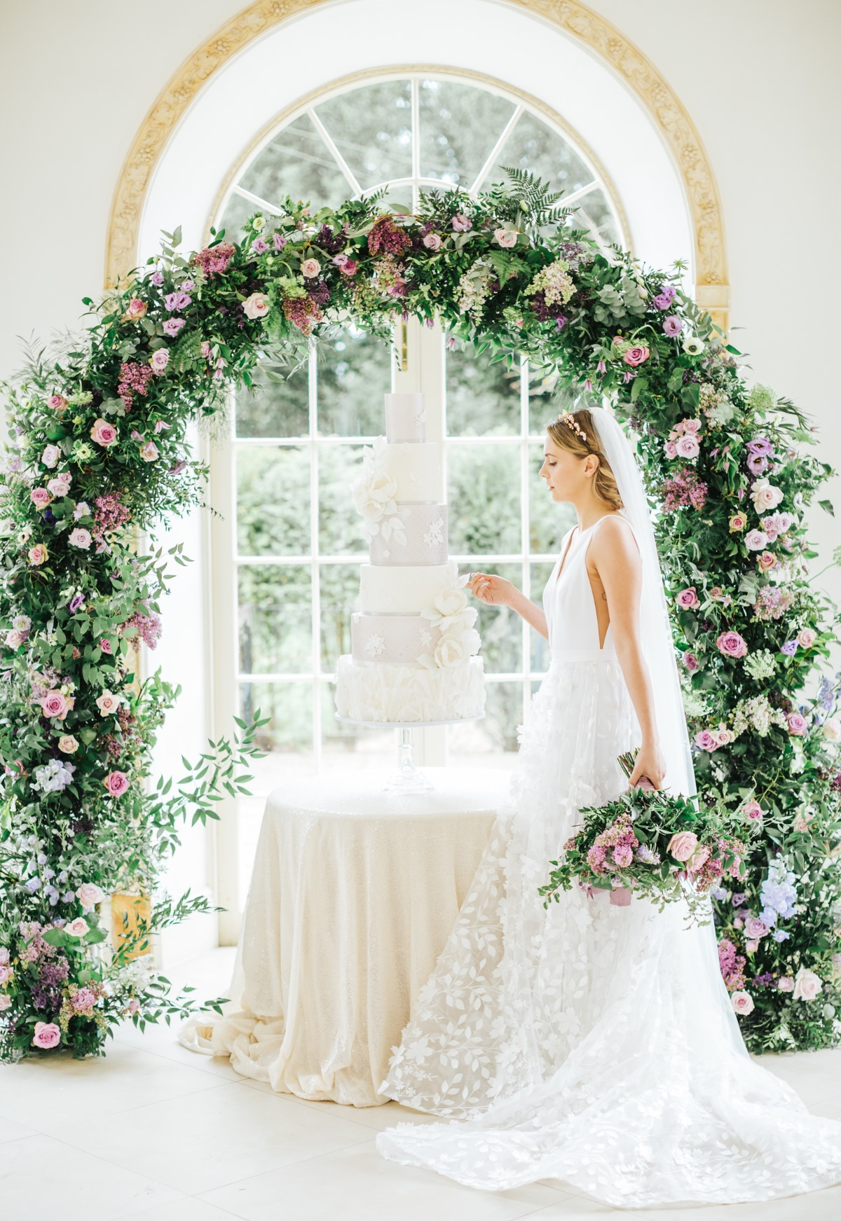 white wedding cake under flower arch