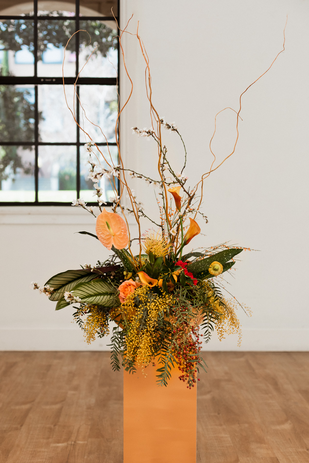 yellow tropical wedding floral arrangement used as aisle decor by New Creations Flower Company