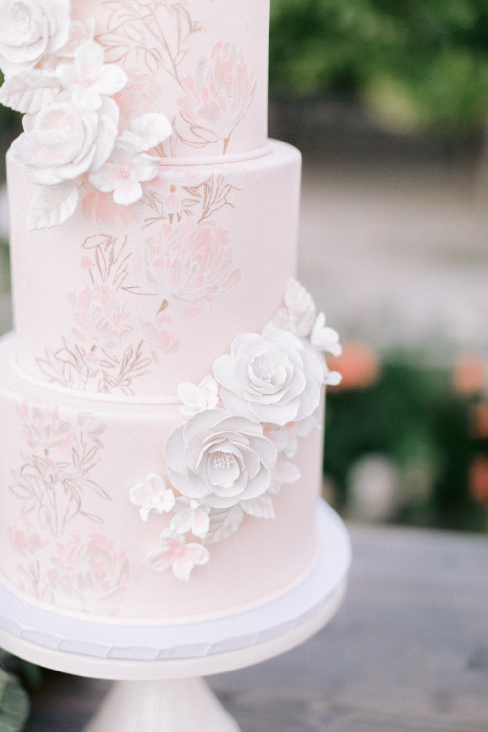 pink wedding cake with white sugar florals