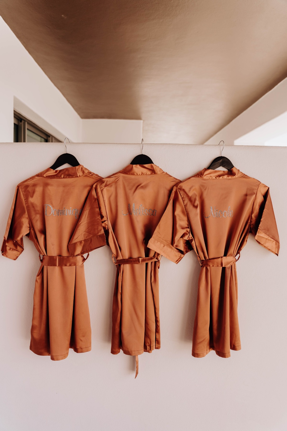 personalized terra cotta bridesmaid robes with their names in glitter.