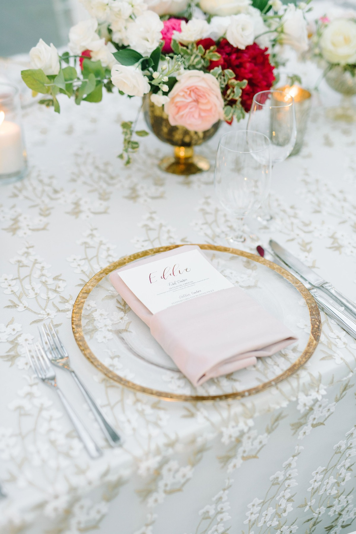 clear gold rimmed chargers with blush napkins for table setting