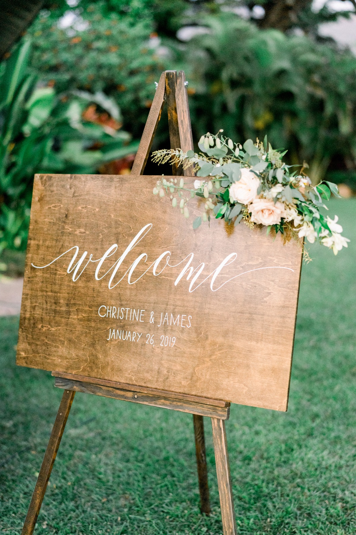wooden welcome wedding sign adorned with flowers