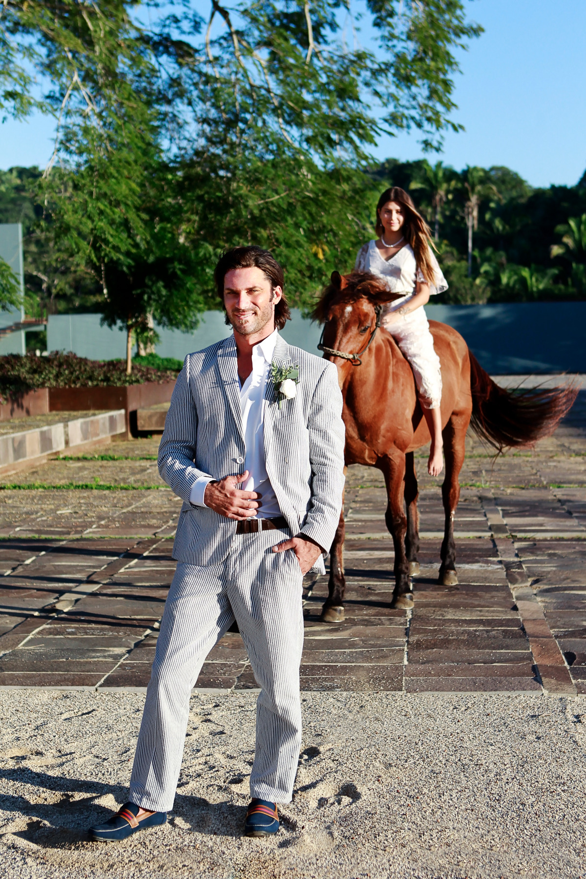 Groom awaits for his bride as she arrives on horseback