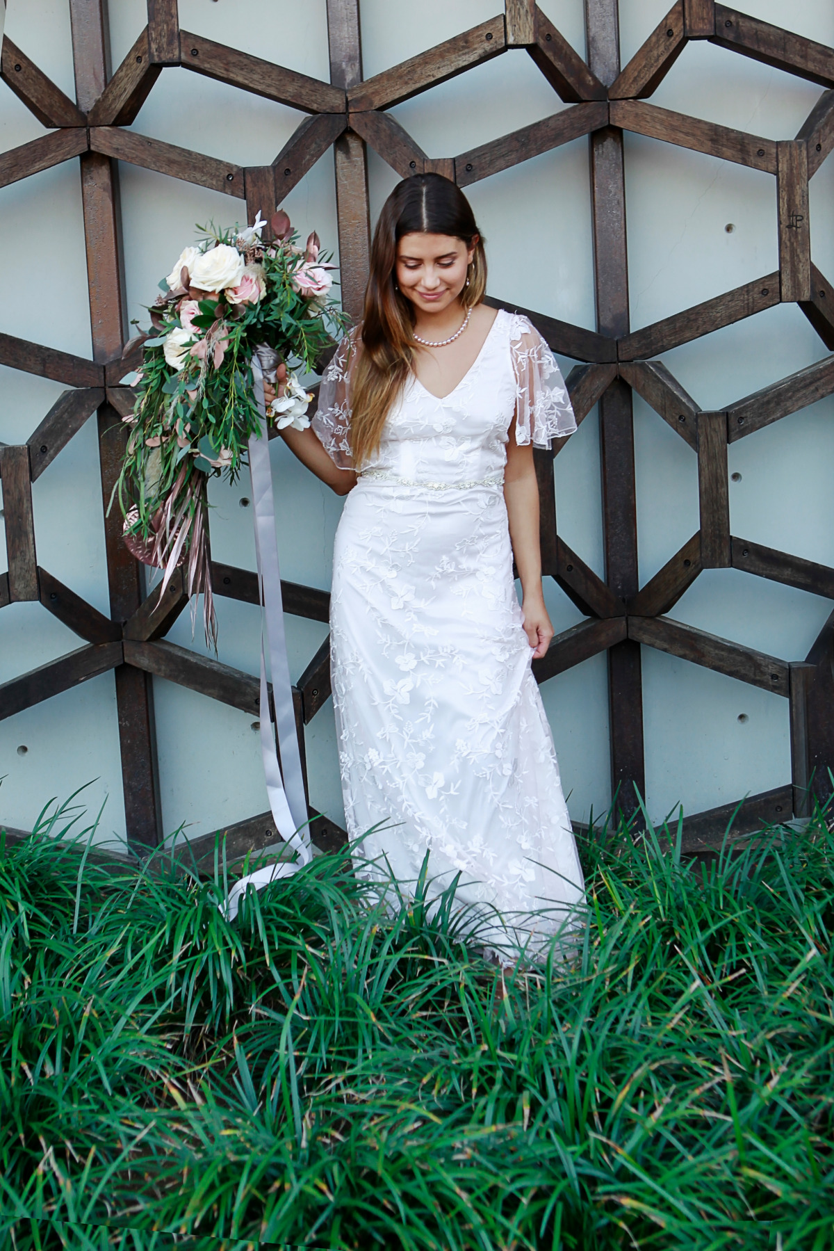 lace wedding dress with sleeves and pink wedding bouquet