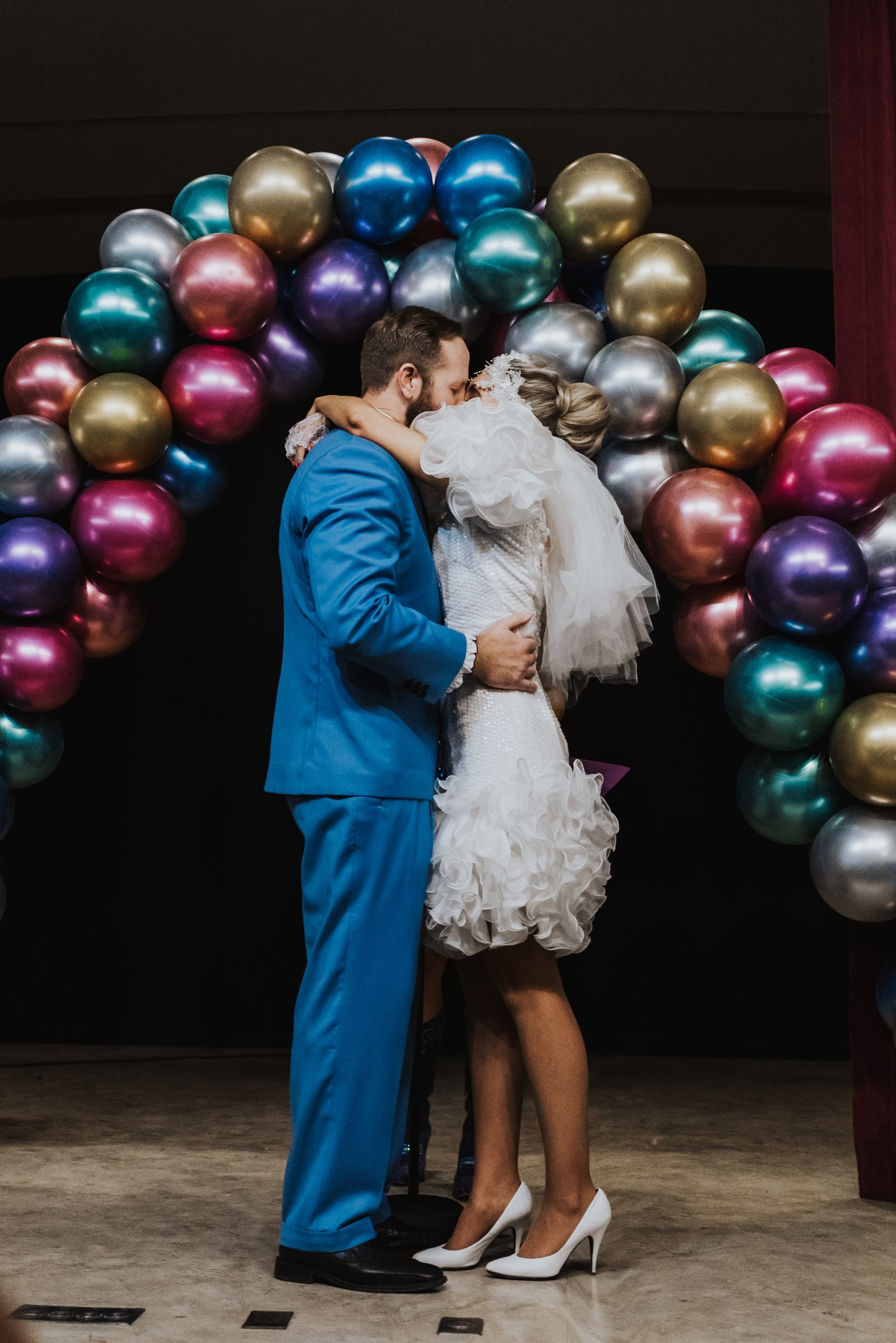 first kiss under a balloon arch at this 80's inspired costume wedding