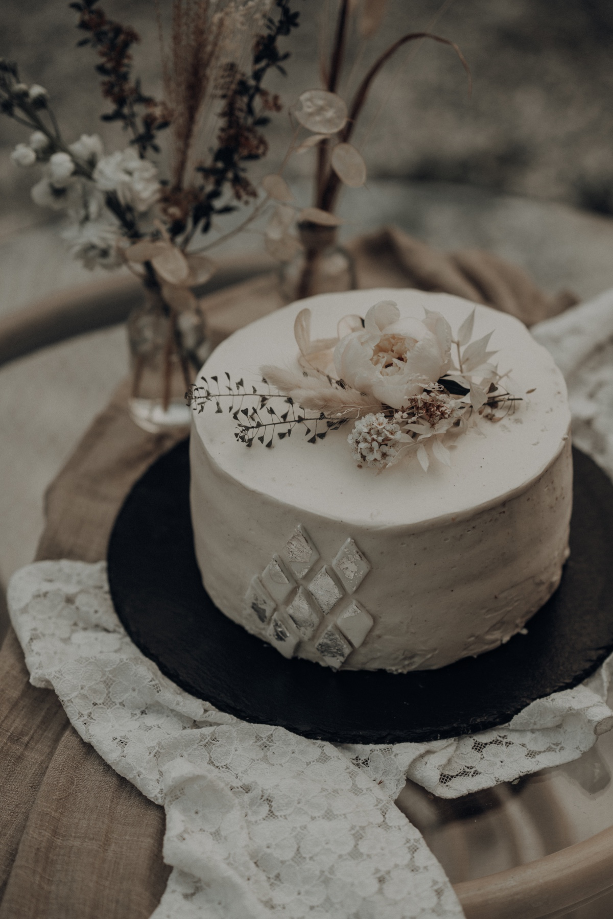 white wedding cake with dried flowers