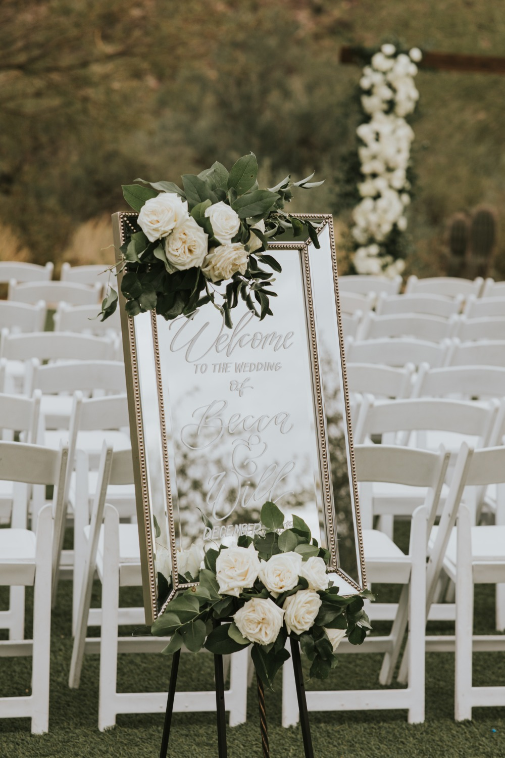Mirror wedding sign adorned with florals