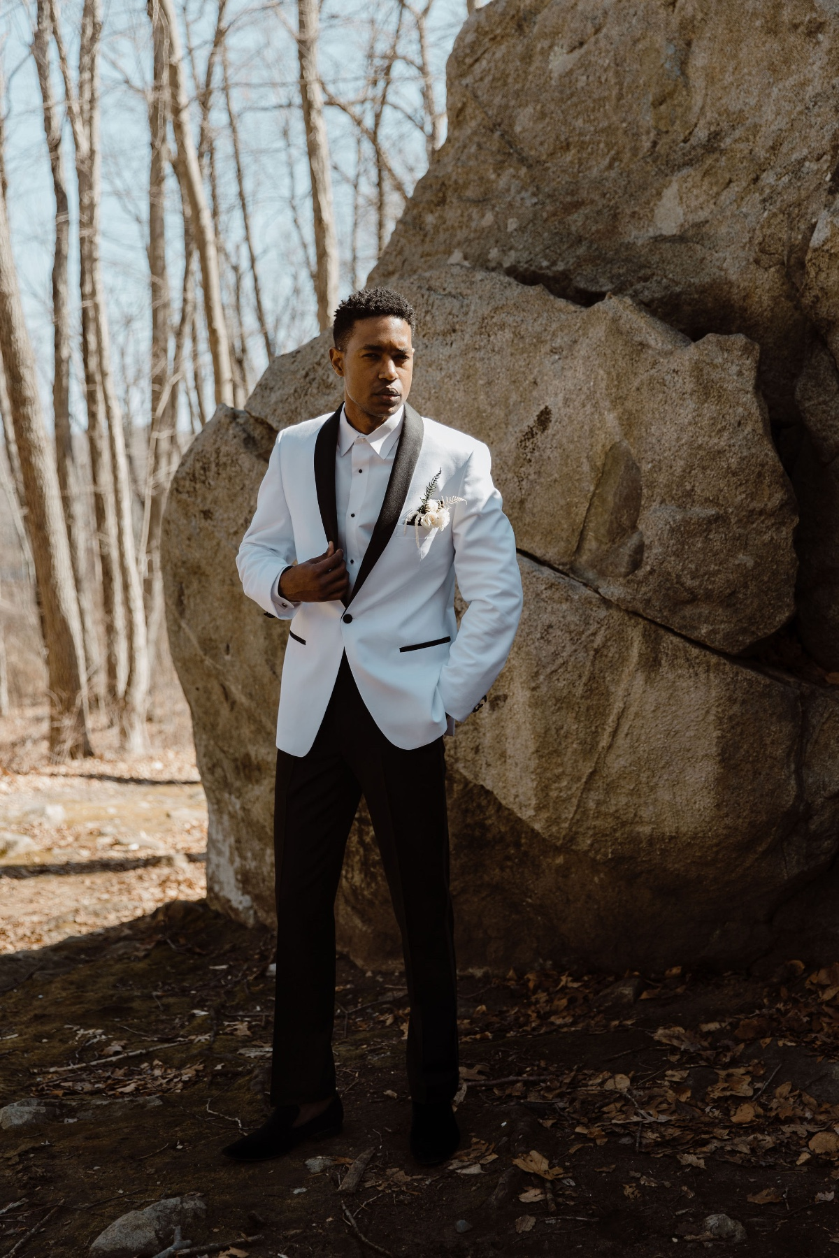 groom in white suite with black trim and rose boutonnière from Aldo's House Of Formals