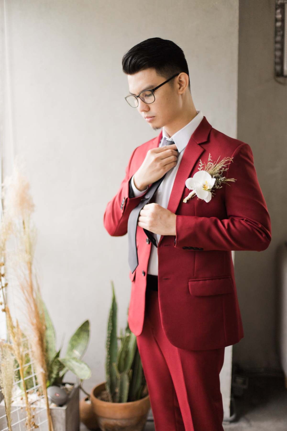 groom in wine colored suit with black tie and orchid boutonniere