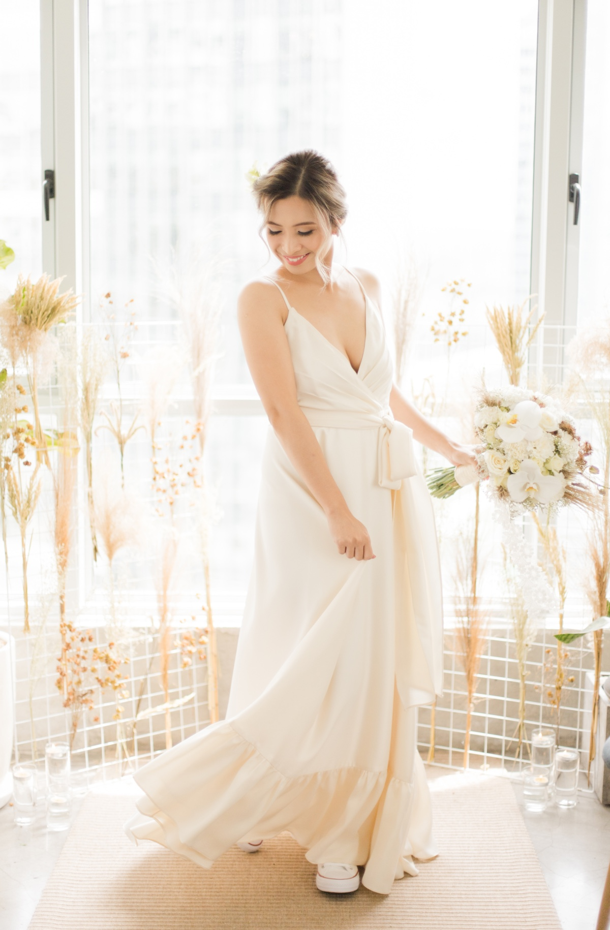 bride in wrap around dress with orchid wedding bouquet
