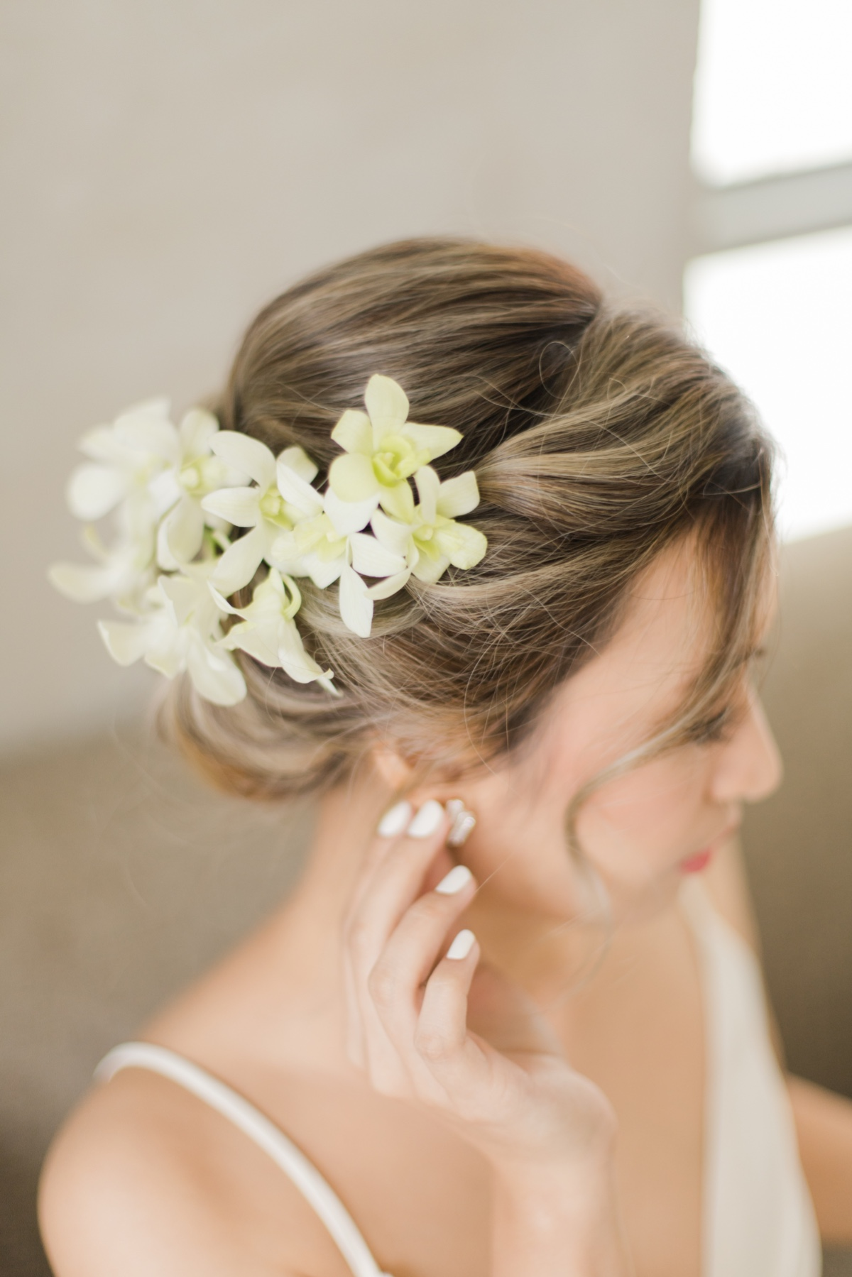 bride has an updo with orchids in her hair