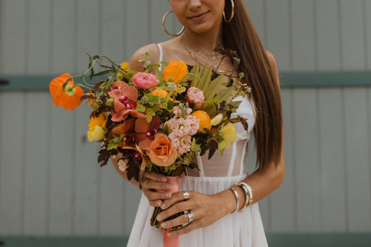 colorful wedding bouquet with orchids, oranges, garden roses