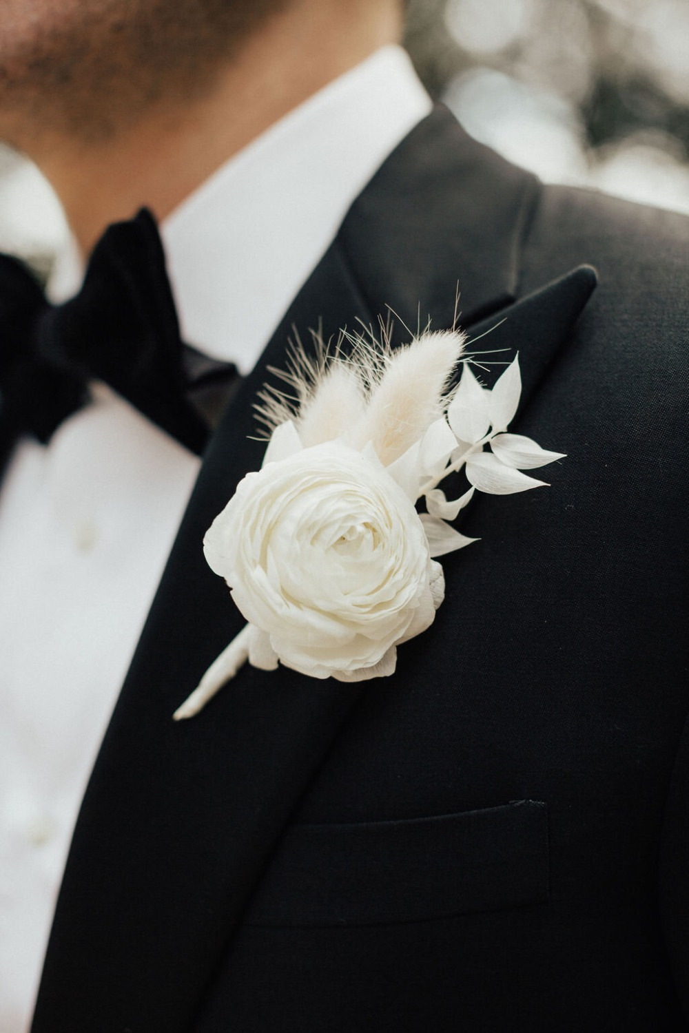 groom in black tux with white boutonnière